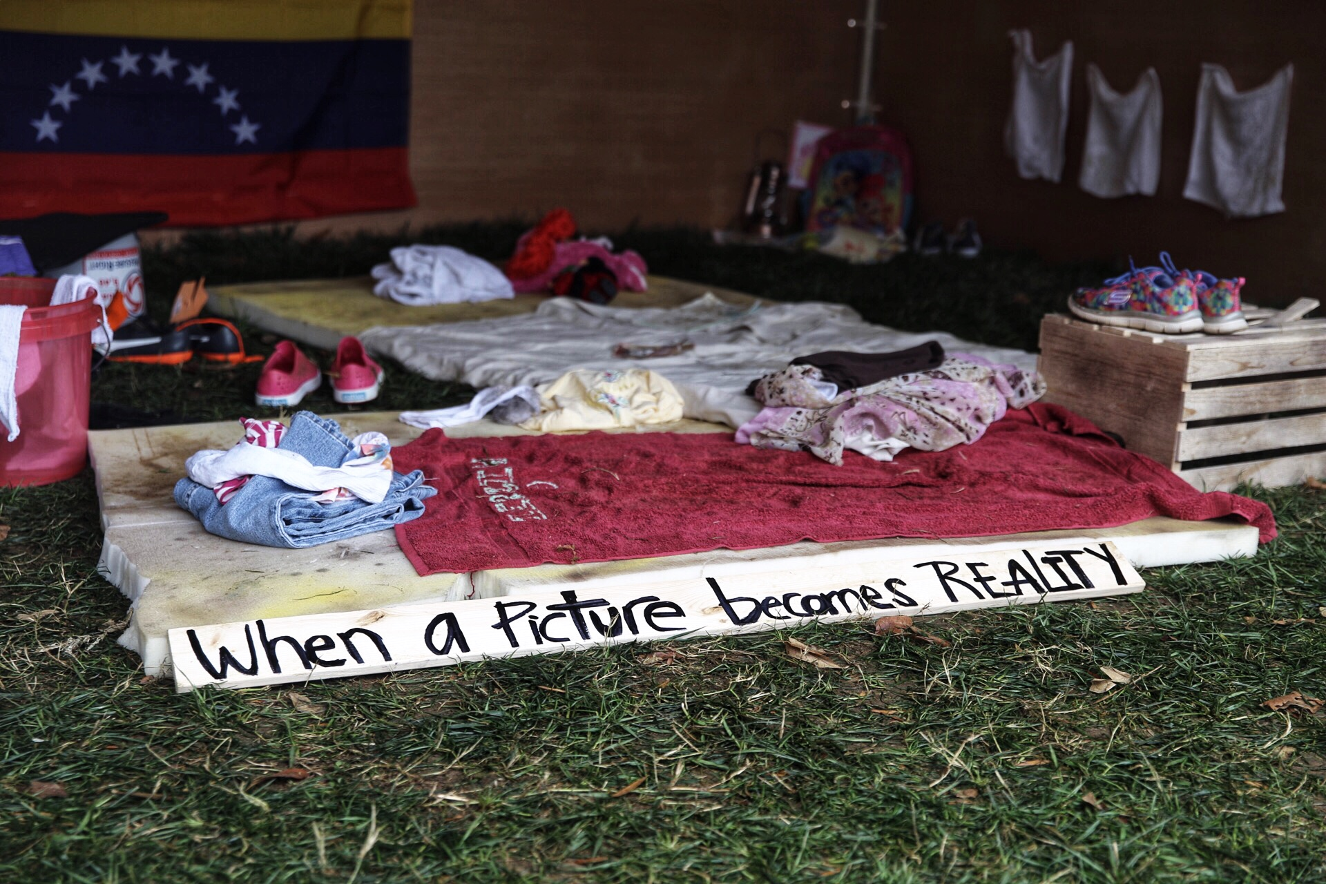 Interior of a tent showcasing the current humanitarian crisis in Venezuela with dirty mattresses, torn towels, ripped clothing, shoes with no laces, an empty water jug, and a pair of children's stuffed animals.